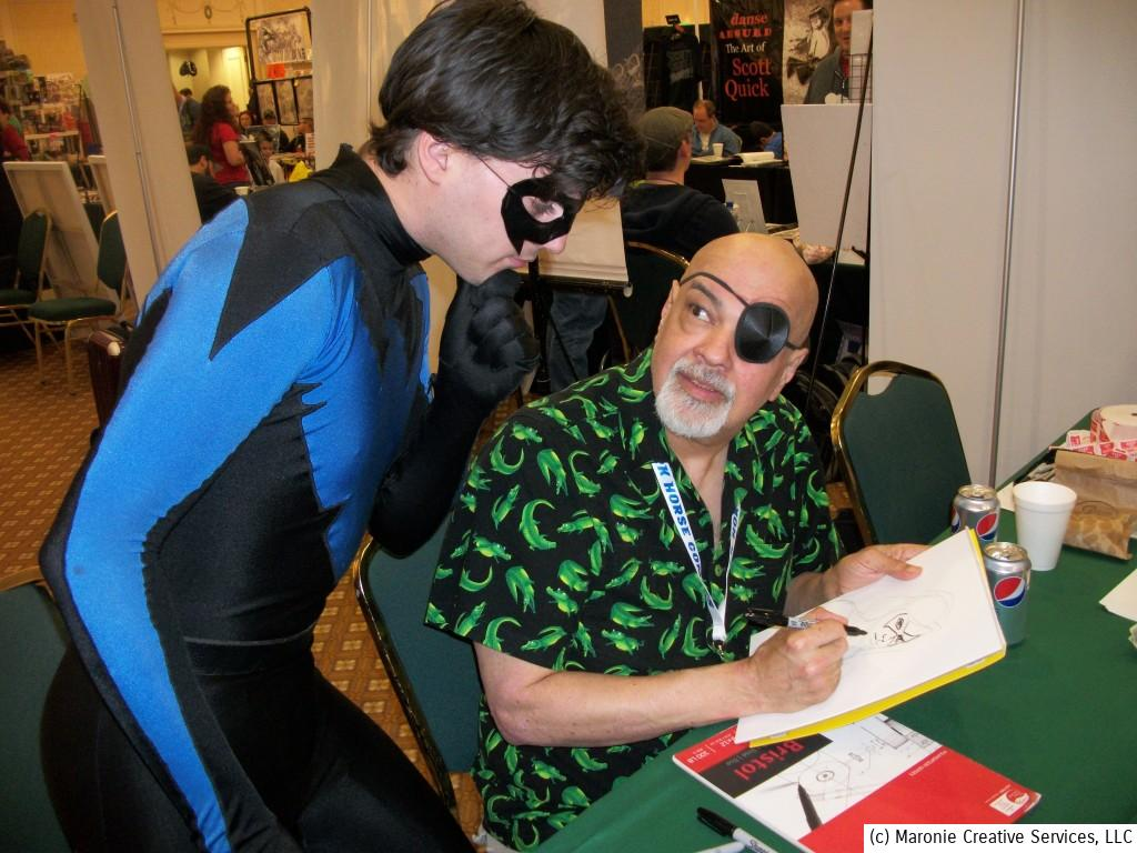 Nightwing peers over George Perez's shoulder as the artist works on a sketch.