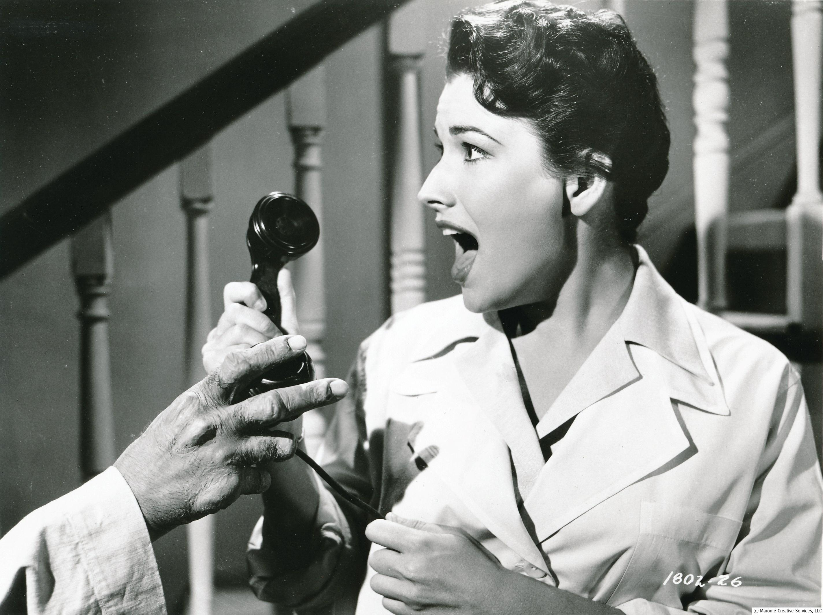 SORRY, WRONG NUMBER! Mara Corday takes a call for Leo G. Carroll in a tense scene from Tarantula. Too bad they didn't have cell service then!