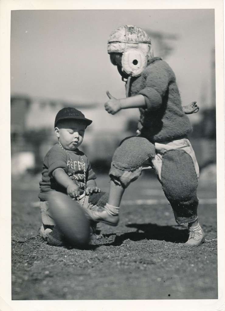 Chubby-cheeked Spanky of the Little Rascals holds the football while a fellow-player attempts a punt. One expects him to yank the ball away at the last second, a la Lucy from the Peanuts comic strip.