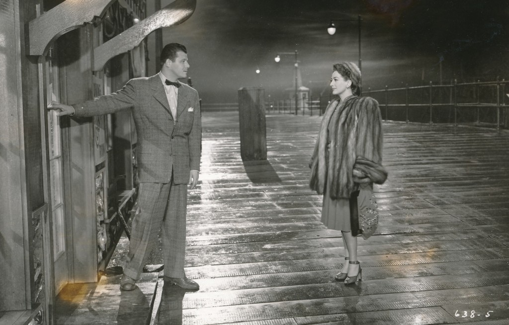 A very 'noir' scene from Joan's greatest triumph, Mildred Pierce. She won a deserved Oscar for her performance in this film, after she was considered washed-up by theater exhibitors and went to Warner Brothers with her tail between her legs. (c) Warner Brothers. That's the great Jack Carson with her.