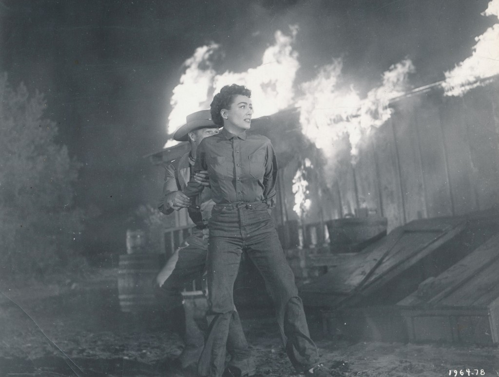 JOAN ON FIRE! This exciting photo is from Joan's western for Republic Studios, Johnny Guitar. Besides being a well-made film, the production was rife with conflict as Joan and co-star Mercedes McCambridge detested each other and fought constantly----just like their characters did in the movie. (c) Republic