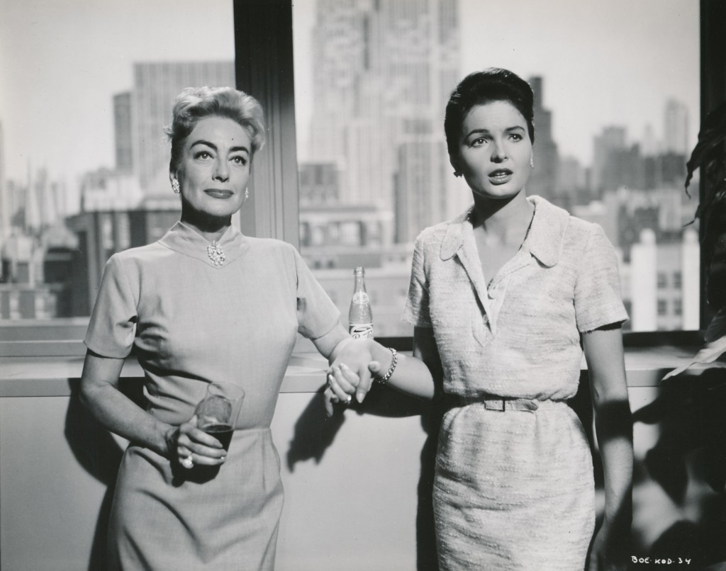 This still from The Best of Everything is notable for many reasons. Joan is locking hands with Diane Brewster, who JC later recommended as her co-star in Straightjacket. Please be sure to note the bottle of Pepsi on the ledge behind them! (c) 20th Century-Fox