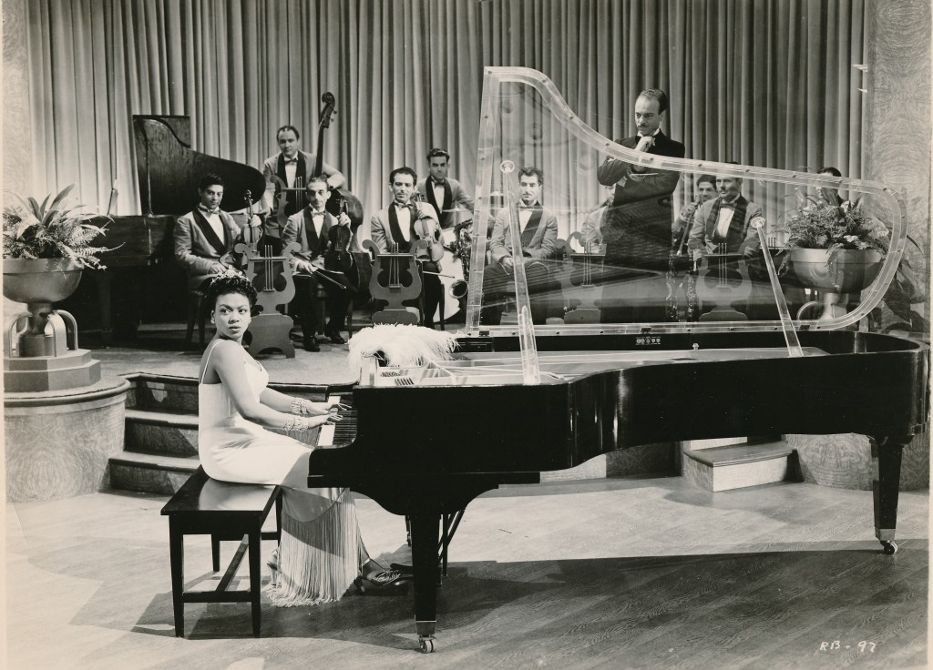 The always-glamorous Hazel Scott performs in a segment of the all-star Waner Bros. film, Rhapsody in Blue. Ms. Scott appeared in several Hollywood films. Unfortunately these performances were confined to 'segments' that could be edited out of prints shipped to sensitive Southern states.  (c) Warner Brothers