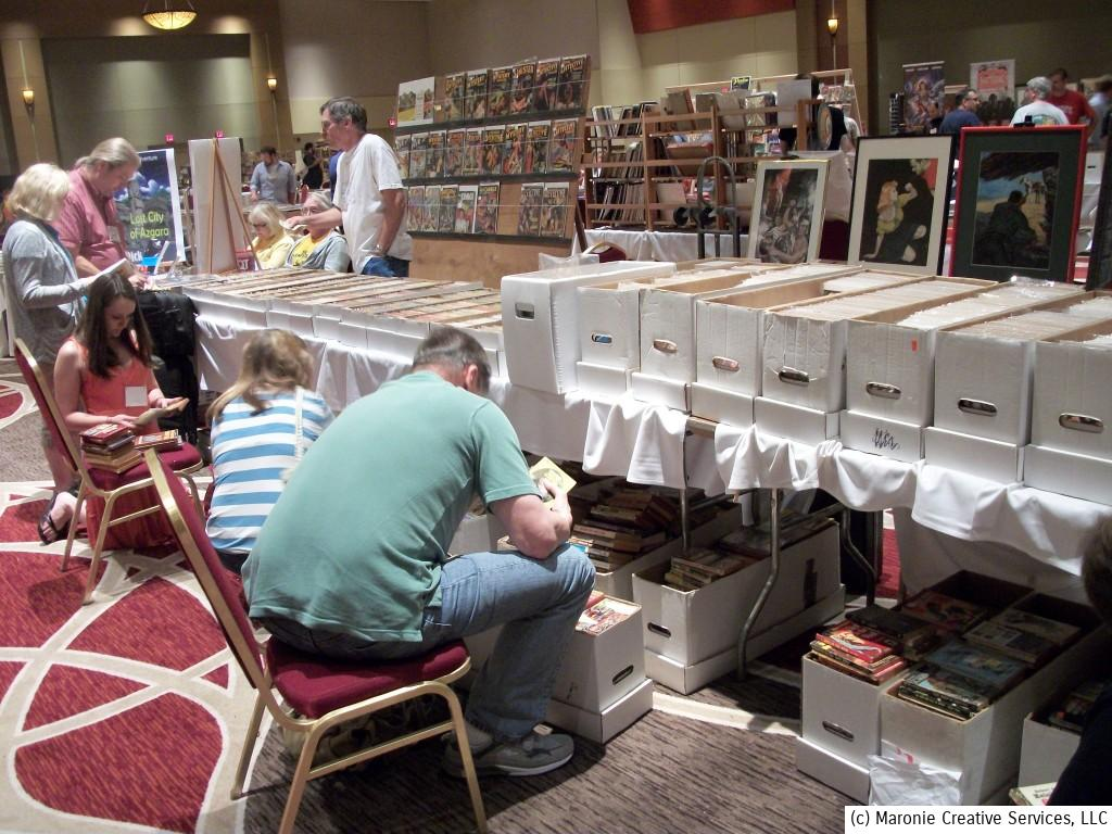 Collectors patiently comb through the boxes of vintage paperbacks, looking for a treasure.