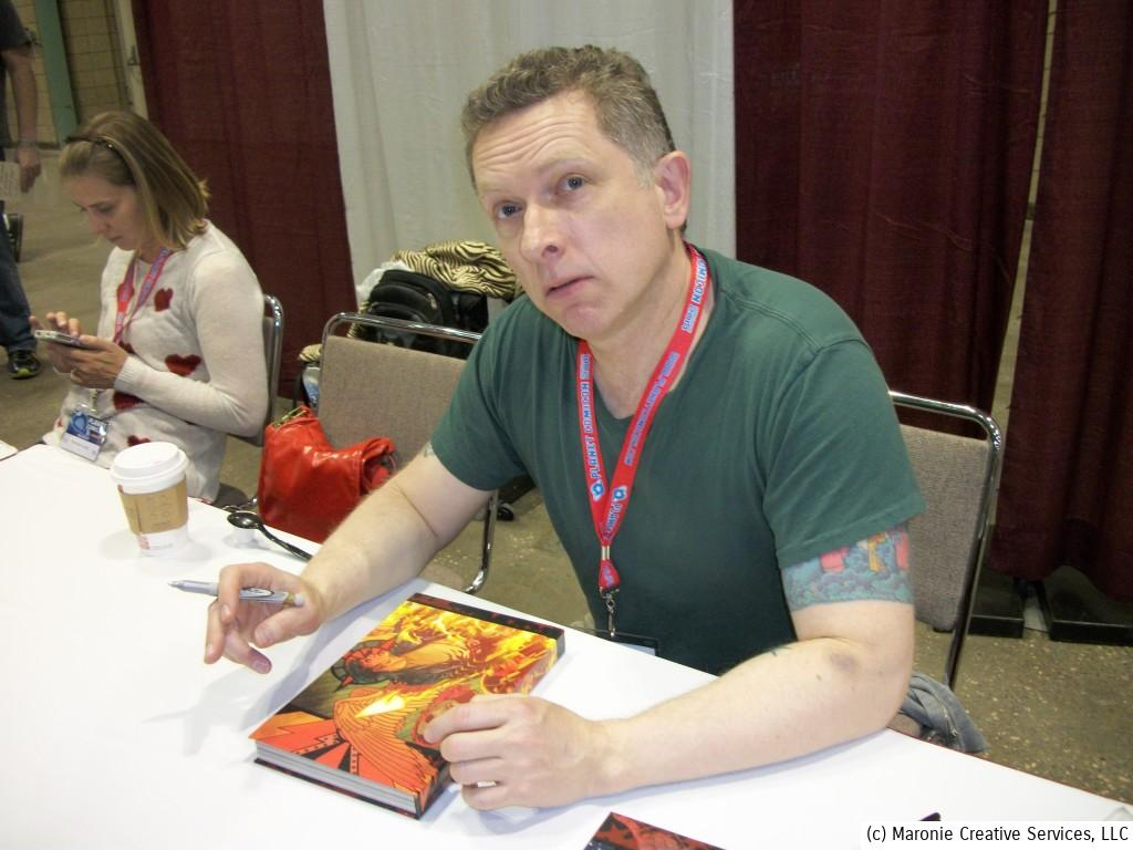British writer James Robinson, scribe of 'Starman' and other high-profile projects, pauses to sign another book for a fan.