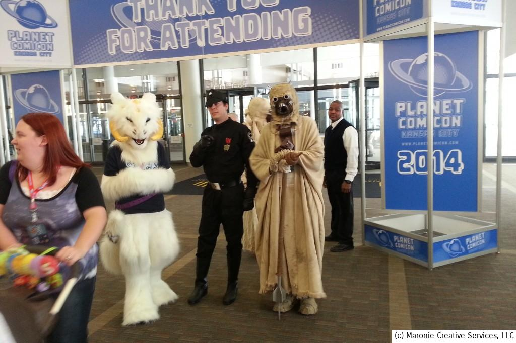 A costumed welcoming committee greets fans as they enter Planet Comicon 2014. Don't you love the expression on the face of the convention center worker on the right?