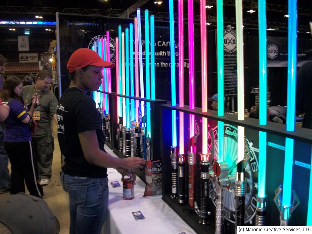 A young fan takes his pick from a display of multi-colored light sabers.