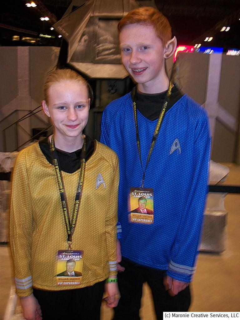 Two youthful 'Trekkies' proudly show off their pointed ears.  Badges indicate they are signed up for the William Shatner 'experience'. Stop and realize the original Star Trek had been off the air for almost 30 years before these young 'uns were even born!