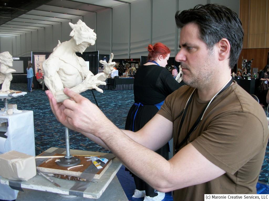 A sculptor demonstrates fashioning a bizarre creature from wires and clay. Visitors had the opportunity to view the creation from start to finish.