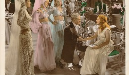 'I Married An Angel,' was the last teaming of Nelson Eddy and Jeanette MacDonald. Eddy is down on one knee with MacDonald, while a bevy of costumed beauties look on. (c) MGM