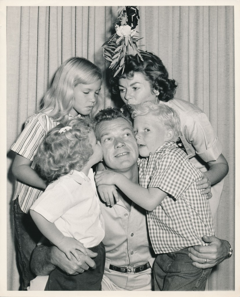 Young whippersnapper William Katt hugs his famous father, Bill Williams, while mom Barbar Hale and the rest of the family look on.