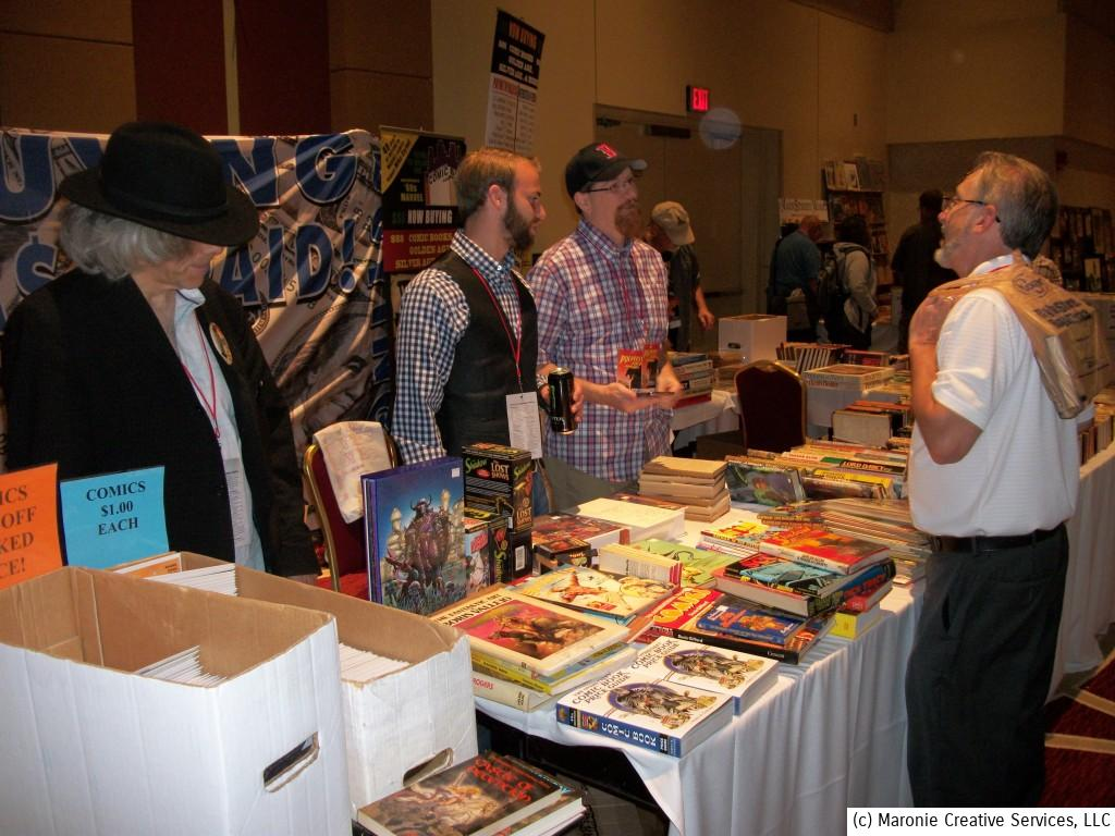 New Jersey megadealer Michael Carbonaro (l) mans one of the most active tables during Pulpfest 2014. Carbonaro was a whirling dervish of activity during the show, unpacking box after box of musty treasures for sale. That's Columbus dealer Doug Simms in the baseball cap on the right.