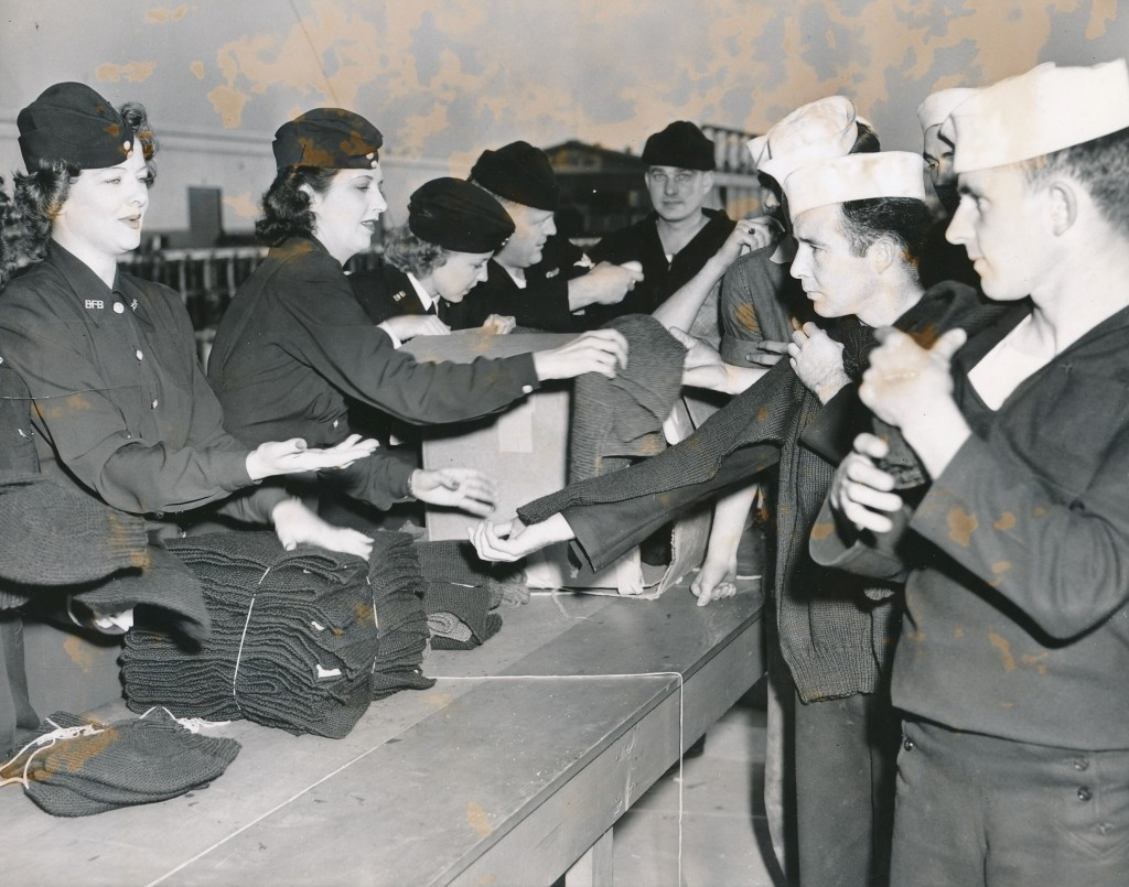 During World War II Ms. Loy and actress Kay Francis distribute knitted goods to Uncle Sam's Navy Bluejackets.