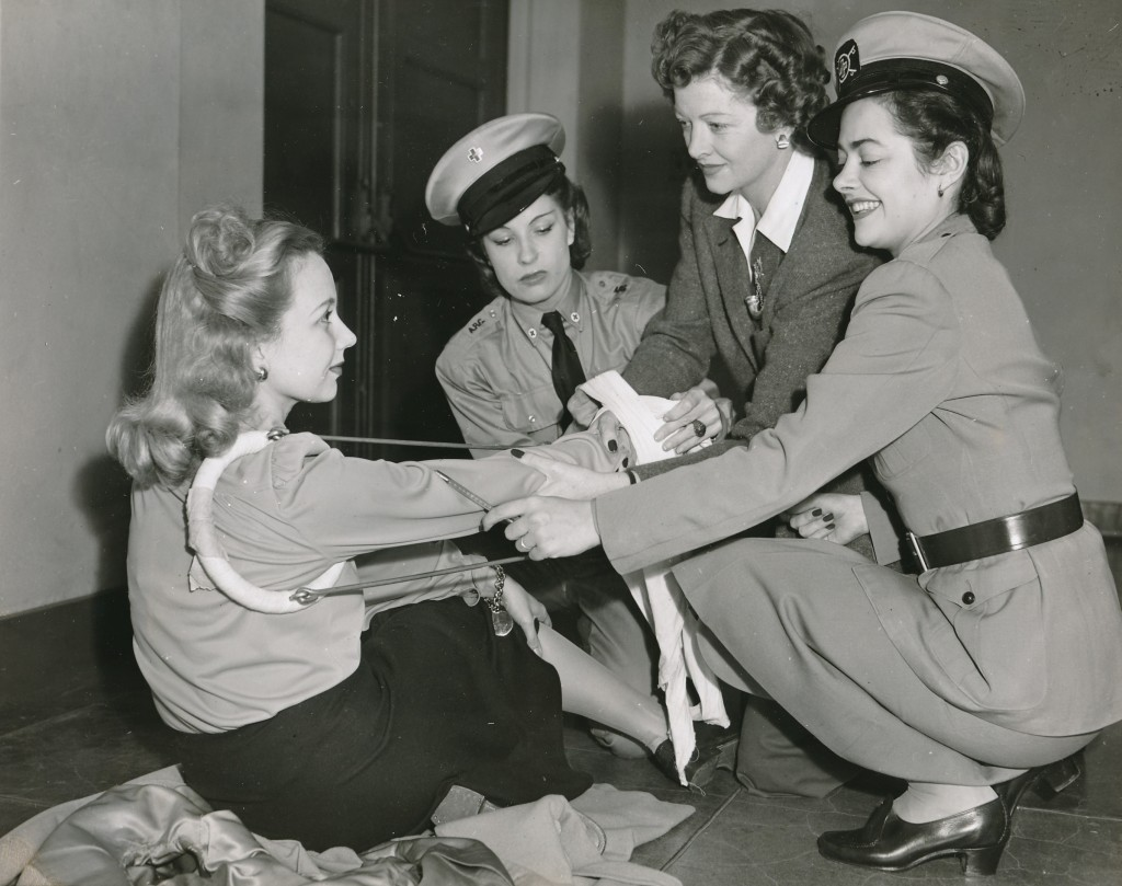 Myrna was a tireless volunteer for a variety of causes. Here she wraps fellow-actress Ann Sothern in first-aid bandages while Lili Damita (l) and a Red Cross instructor (r) assist.