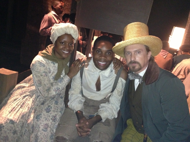 Gogo Lomo-David poses for the still photographer flanked by his screen wife, Brandi Feemster (l) and slave-trader John Rixey Moore (r).