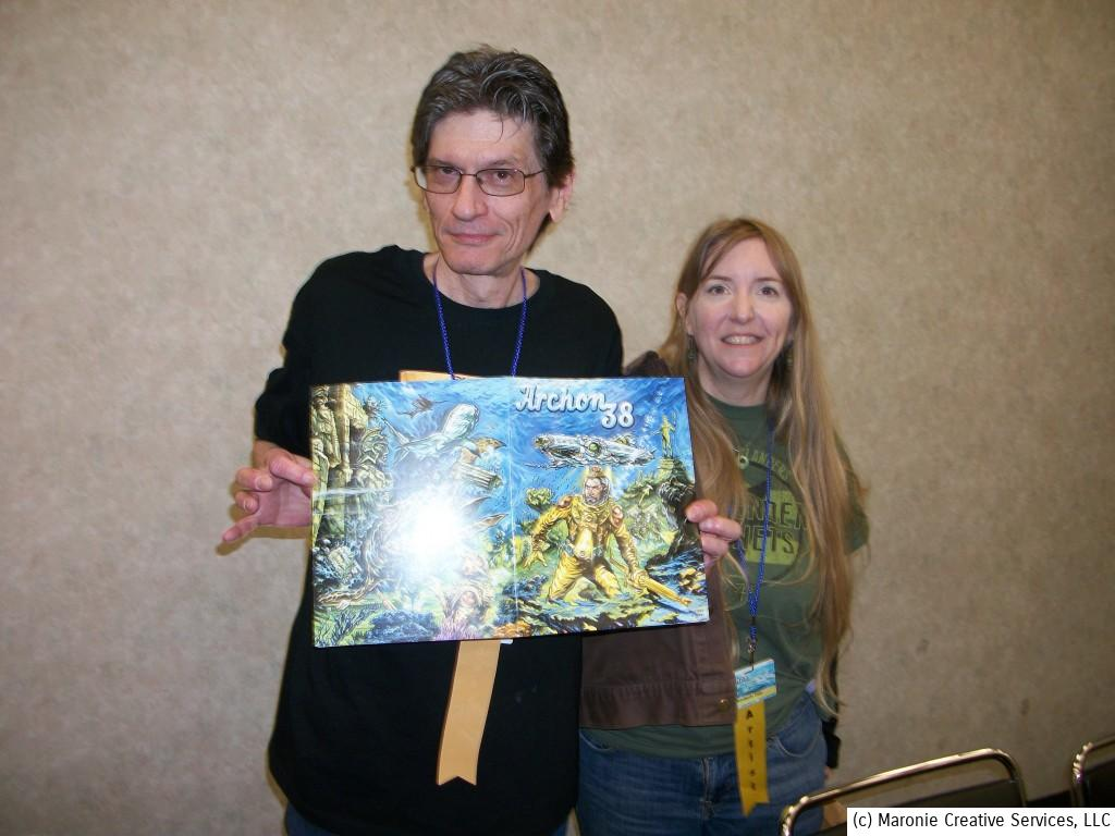 Archon Artist Guest of Honor Paul Daley displays his program cover art. He's flanked by wife Kim.
